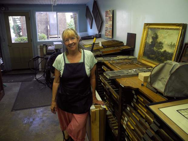 Judith Berliner of Full Circle Press standing beside antique printing equipment owned by her father, Harold Berliner. Photo by Dave Brooksher.