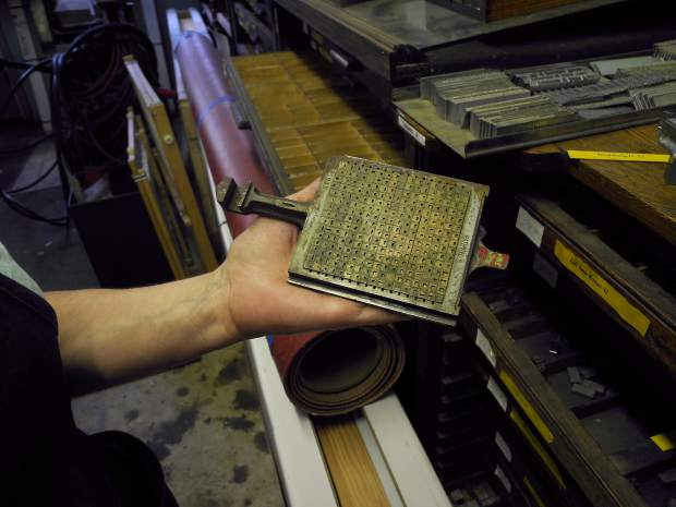 Judith Berliner holds up part of an old linotype machine for examination.
