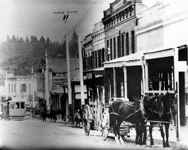 A street car comes up Main Street behind a horse-drawn wagon in downtown Grass Valley.