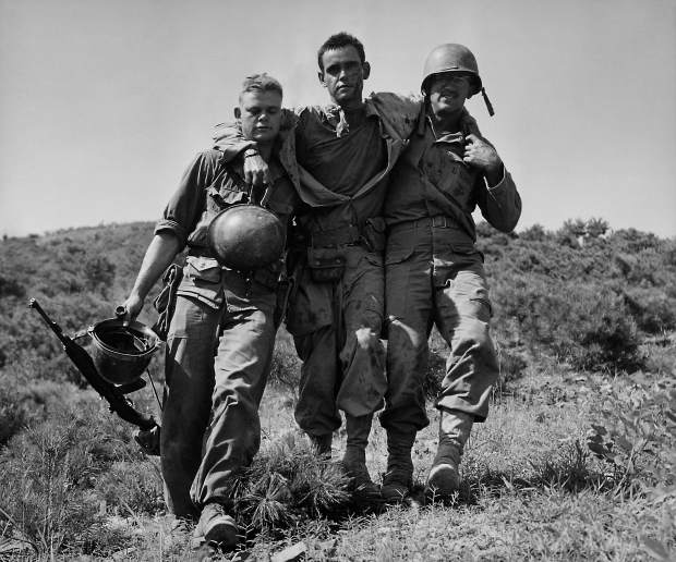 In August 1950 file photo, U.S. Marines help a wounded buddy on the Naktong River front in South Korea.  The war that began in Korea 60 years ago, on June 25, 1950, a ghastly conflict that killed millions and left the peninsula in ruins, became
