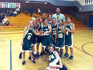 The Magnolia seventh grade girls basketball team claimed the Nevada County seventh grade tourney title. Front laying down is Maddi Brown.