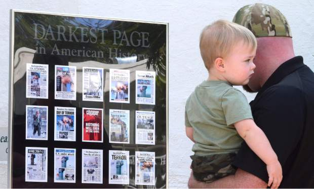 Scott Goin and son Hunter view the display of newspaper front pages from the day after the 9/11 disaster.