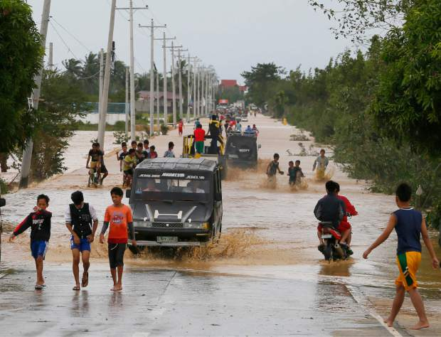 Residents wade through raging floodwaters brought about by Typhoon Koppu at Zaragosa township, Nueva Ecija province, north of Manila, Philippines Monday, Oct. 19, 2015. Slow-moving Typhoon Koppu blew ashore with fierce wind in the northeastern Philippines early Sunday, toppling trees and knocking out power and communications and forcing the evacuation of thousands of villagers.(AP Photo/Bullit Marquez)