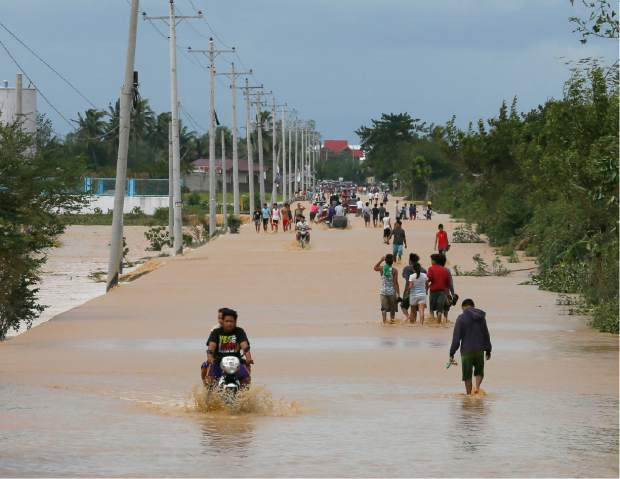 Residents wade through floodwaters brought about by Typhoon Koppu at Zaragosa township, Nueva Ecija provinc,e north of Manila, Philippines Monday, Oct. 19, 2015. Slow-moving Typhoon Koppu blew ashore with fierce wind in the northeastern Philippines early Sunday, toppling trees and knocking out power and communications and forcing the evacuation of thousands of villagers.(AP Photo/Bullit Marquez)