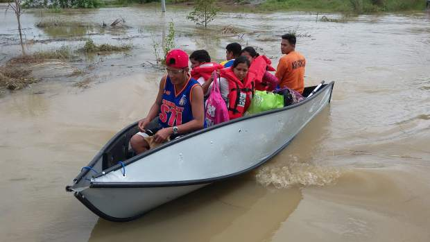 In this photo provided by the Philippine Air Force, a family rides a small boat after being rescued by members of the Philippine Air Force as they evacuate families trapped in flooded villages in Isabela province, northern Philippines on Monday Oct. 19, 2015. Army, police and civilian volunteers scrambled Monday to rescue hundreds of villagers trapped in their flooded homes and on rooftops in a northern Philippine province battered by slow-moving Typhoon Koppu. (Staff Sgt. Ismael Y Amlhasan, Tactical Operations Group 2/Philippine Air Force via AP)