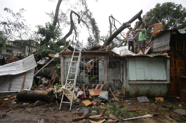 Residents and rescuers stand on top of a damaged house as they cut apart a toppled tree from Typhoon Koppu in suburban Quezon city, north of Manila, Philippines on Monday, Oct. 19, 2015. Army, police and civilian volunteers scrambled Monday to rescue hundreds of villagers trapped in flooded homes and on rooftops in the northern Philippine province battered by slow-moving Typhoon Koppu. (AP Photo/Aaron Favila)