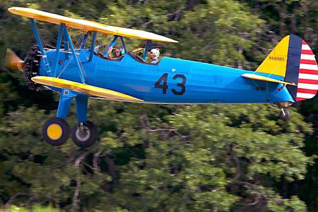 The Boeing Stearman Biplane flys around the airport. A woman waves  to friends on the ground. The Nevada County Airport  hosted a Fly-in and Open House Saturday.