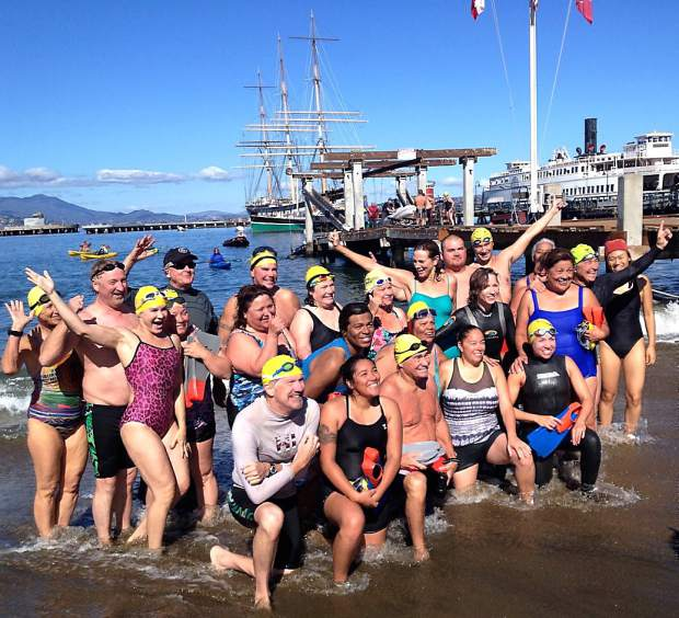 Patricia Smith and other participants of the 13th annual PATHSTAR Alcatraz Swim Week pose for a group photo Monday at Aquatic Park, San Francisco, the destination of their swimathon.