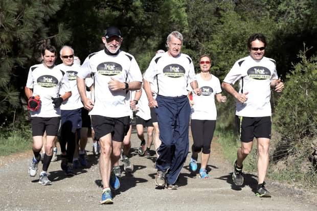 Members of the Trkac Racing Team warm up with teammate Geno Meyers, third from right, who continues to run competitively despite being diagnosed with early onset of Alzheimer's disease.