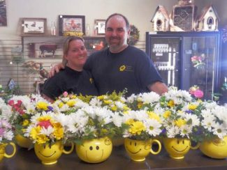 Co-owners of Forever Yours Florist & Gifts Mark and Sally Heer with the Be Happy mug flowers they presented to residents at the Golden Empire Nursing & Rehap Center.