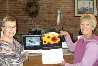 Jayne Sanchez (left) of MAJR Specialties presents raffle winner Anne Starr with 100 business calendars, each imprinted with the Sierra Starr logo.