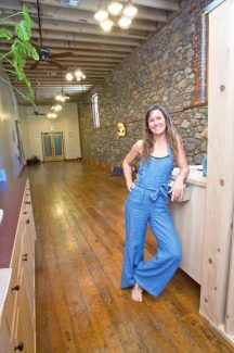 Mandy Lucchese, owner of KinFolk Yoga, poses for a photo in her new studio in in the historic Alpha Building in downtown Grass Valley.