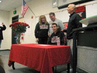 Bear River volleyball and basketball player Justin Beskeen, flanked on the left by his parents and on the right by Athletic Director Duwaine Ganskie, signs his letter of intent to play volleyball at California State University, Northridge, next year.