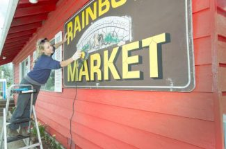 Sarah Coleman, Owner of Painted Bird Studio, preparing the Rainbow Market sign to be repainted.  The Rainobw Market is located on Highway 49, across from the Willo Restaurant.