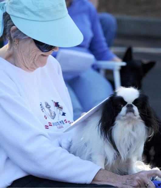 A woman reads as she waits for her turn to have her dog blessed at Saturday's Blessing of the Animals at Peace Lutheran Church in Grass Valley.