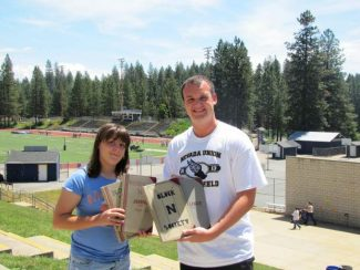 Nevada Union student athletes Shelby Dilorenzo, left, and Kyle Cammon stand outside Hooper Stadium holding ledgers from Block N Club meetings in the 1950s, 60s and 70's.  Current Nevada Union student-athletes have resurrected the club, and will provide community service to various Nevada County groups.