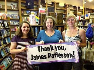 The Book Seller staff members Brittany Blake (left), Angie Kelse and Tyrra Courtney (right), hold a sign at the store thanking author James Patterson for giving the store a grant to renovate the children's book section.