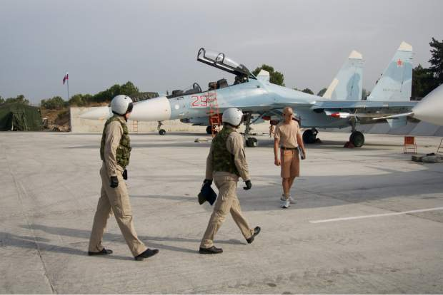 Russian pilots walk to their Su-30 jet at Hemeimeem airbase, Syria, on Thursday, Oct. 22, 2015. Since early morning, Russian combat jets have been taking off from this base in western Syria, heading for missions. (AP Photo/Vladimir Isachenkov)