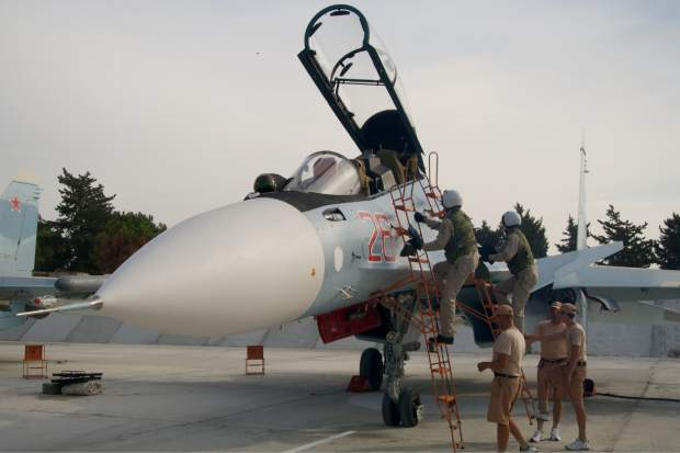 Russian pilots climb to their Su-30 jet at Hemeimeem airbase, Syria, on Thursday, Oct. 22, 2015. Since early morning, Russian combat jets have been taking off from this base in western Syria, heading for missions. (AP Photo/Vladimir Isachenkov)