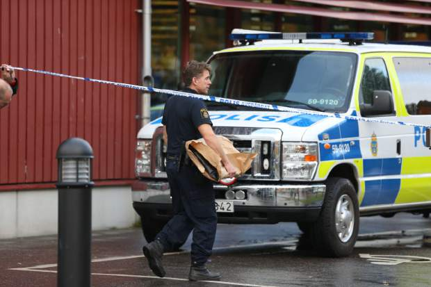 A policeman carries evidence bags as he leaves the crime scene following a knife attack at a school Thursday Oct. 22, 2015, in Trollhatten, Sweden. A knife-wielding masked man stabbed four people Thursday at a school in southern Sweden, killing one teacher and a student before being shot by police, authorities said. (AP Photo/Bjorn Larsson Rosvall)   SWEDEN OUT