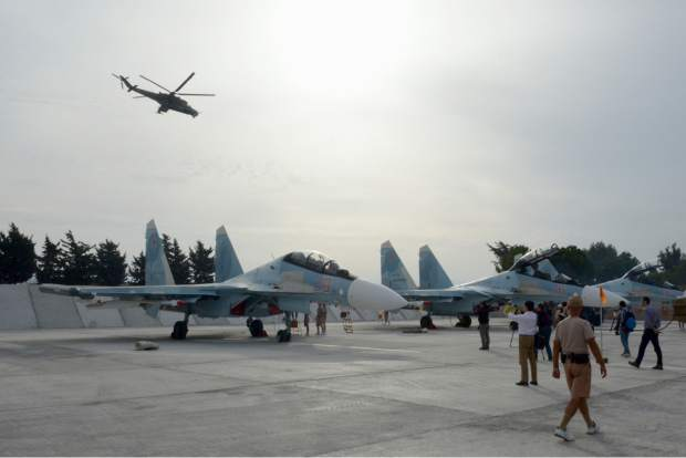 Journalists film Su-30 jets parked at Hemeimeem airbase, Syria, on Thursday, Oct. 22, 2015, as  Mi 24 helicopter gunship flies overhead. Since early morning, Russian combat jets have been taking off from this base in western Syria, heading for missions. (AP Photo/Vladimir Kondrashov) 2