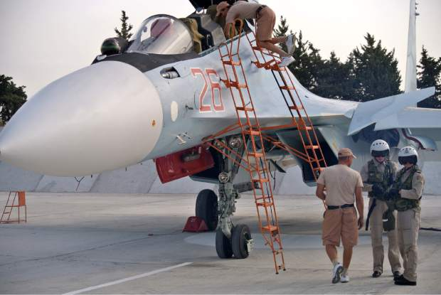 Russian air force crew stand next to a fighter jet in preparation for a combat mission at Hemeimeem airbase, Syria,  Thursday, Oct. 22, 2015. Since early morning, Russian combat jets have been taking off from this base in western Syria, heading for missions. (AP Photo/Vladimir Isachenkov)