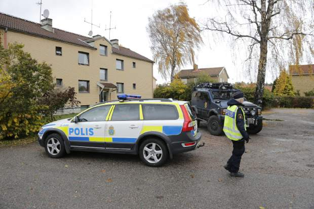 Police cars are parked outside the house where the suspected attacker lives, after a knife-wielding masked man left two dead and several wounded at a school in Trollhattan, Sweden, Thursday Oct. 22, 2015.  A knife-wielding masked man stabbed four people Thursday at a school in southern Sweden, killing one teacher and a student before being shot by police, authorities said. (Adam Ihse / TT via AP)  SWEDEN OUT