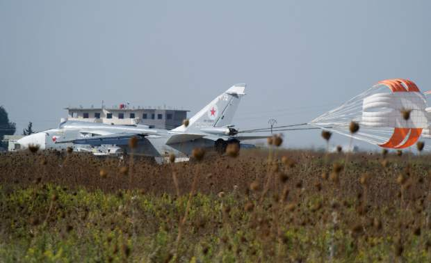 A Russian Su-24 bomber lands at Hemeimeem airbase, Syria, on Thursday, Oct. 22, 2015. Since early morning, Russian combat jets have been taking off from this base in western Syria, heading for missions. (AP Photo/Vladimir Isachenkov)