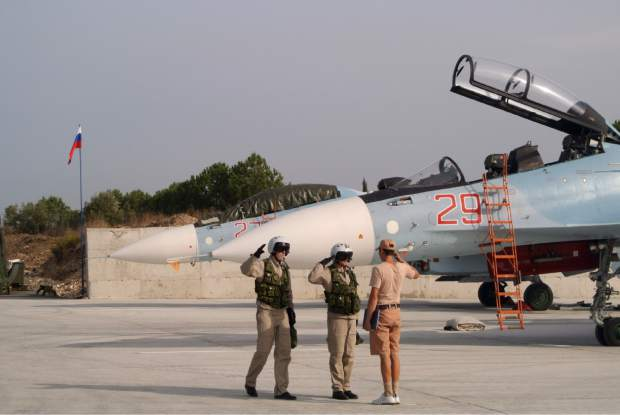 A ground crew member reports to pilots that their jet is ready for a combat mission at Hemeimeem airbase, Syria, on Thursday, Oct. 22, 2015. Since early morning, Russian combat jets have been taking off from this base in western Syria, heading for missions. (AP Photo/Vladimir Isachenkov)