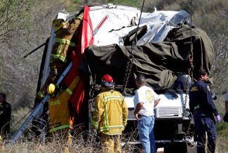A firefighter adjusts a tarp to cover a victim inside after a tow truck lifted a tour bus back onto the road Monday, Feb. 4, 2013, after it collided with two other vehicles and crashed Sunday, killing at least eight people and injuring 38, on Highway 38 just north of Yucaipa, Calif.  The bus was carrying a tour group from Tijuana, Mexico.  (AP Photo/Reed Saxon)