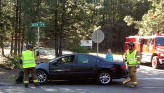 Grass Valley firemen secure the area where a Wednesday morning car crash took place, at the intersection of Highway 49 and Quail Creek Road.