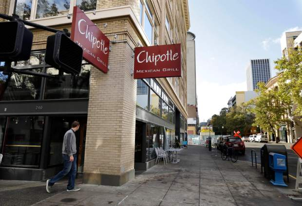 A pedestrian walks past a closed Chipotle restaurant in Portland, Ore., Monday, Nov. 2, 2015. Chipotle voluntarily closed down 43 of its locations in Washington and in the Portland area as a precaution after an E. coli outbreak linked to six of its restaurants in the two states has sickened nearly two dozen people. (AP Photo/Don Ryan)