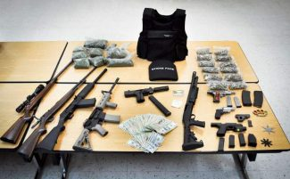 After serving an arrest warrant on  17-year-old  Austin Wallace, Grass Valley Police Department investigators reportedly found pounds of illegal drugs, thousands in cash and a dozen weapons that included an assault rifle, pistols, throwing stars and metal knuckles.