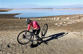 Monica Soares fixes the chain on her bicycle on part of the dry lake bed at Folsom Lake near Folsom Jan. 9, 2014.  Gov. Jerry Brown said he would meet Thursday with his recently formed drought task force to determine if an emergency declaration is necessary as California faces a serious water shortage. Reservoirs in the state have dipped to historic lows after one of the driest calendar years on record.  While still more than 100 yards from the waters edge, Soares is in a spot usually covered in water.