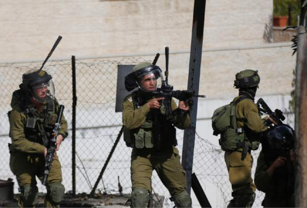 Israeli troops deploy during clashes with Palestinian demonstrators  in Hebron, West Bank, Friday Oct. 30, 2015 A Palestinian stabbed and seriously wounded a man waiting at a light rail station in Jerusalem before he was shot and injured, while in the West Bank two Palestinians charged a checkpoint with knives in their hands, drawing Israeli fire that killed one and wounded the other, police said Friday. (AP Photo/Nasser Shiyoukhi)
