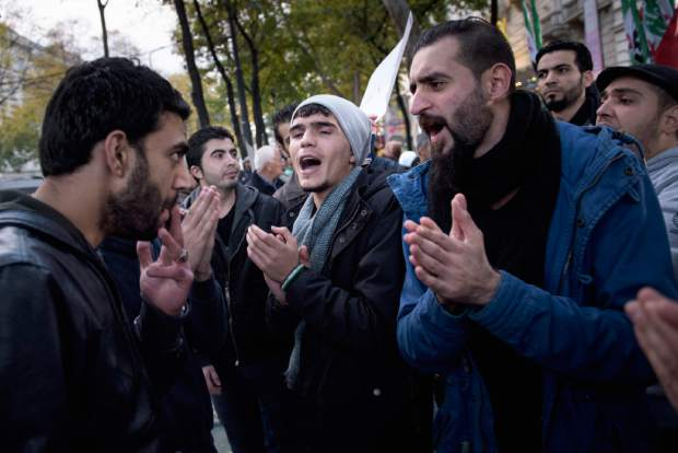 Protesters sing as they gather with others across from the Hotel Imperial in Vienna, Austria, Friday, Oct. 30, 2015, where Secretary of State John Kerry and other diplomats are discussing Syria. The U.S., Russia and other regional and world powers were considering a new plan Friday to set up a ceasefire in Syria within the next four to six months, followed by the formation of a transition government featuring President Bashar Assad and opposition members, officials told The Associated Press.  (Brendan Smialowski/Pool via AP)