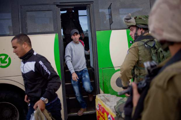 Israeli soldiers watch as Palestinians exit a bus stopped by a checkpoint near the West Bank town of Nablus, Friday, Oct. 30, 2015. Two Palestinians carrying knives ran toward another checkpoint nearby, drawing fire from troops who killed one and critically wounded the other, according to police and a Palestinian medic. (AP Photo/Ariel Schalit)