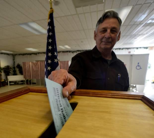 William Nebelski, member of the Hinsdale, N.H., board of selectmen, places peoples ballots into the ballot box at the Hinsdale, N.H. polling station during the New Hampshire primary on Tuesday, Feb. 9, 2016. (Kristopher Radder/The Brattleboro Reformer via AP)