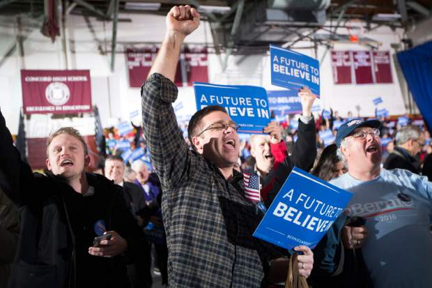 Supporters of Democratic presidential candidate Sen. Bernie Sanders, I-Vt., cheer as a news program announces Sanders as the winner of the New Hampshire primary during a watch party at Concord High School, Tuesday, Feb. 9, 2016, in Concord, N.H. (AP Photo/John Minchillo)