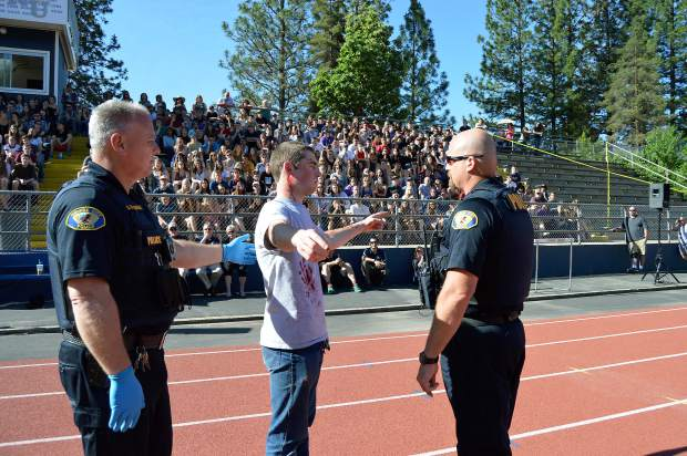 Law enforcement officers lead a student depicting a driver in a mock collision through a field sobriety test Wednesday morning at Nevada Union High School as part of the Every 15 Minutes program.