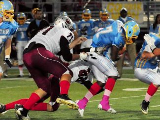 Cannon Fetter and Travis Whitehead try to corral Center quarterback Tyrel Anderson.