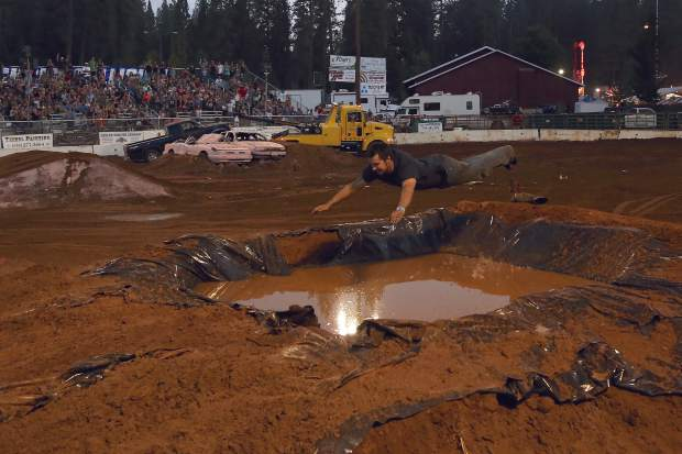 While his truck is towed away, one Tuff Truck contestant belly flops into the pond at the Nevada County Fair on Friday.