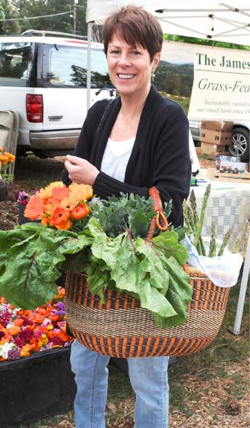 The first Nevada County Certified Growers Market was held Saturday morning at the North Star House, Auburn Road in Grass Valley. Other farmers' markets will also open soon, starting May 5 at the Rood Center, and May 7 in Penn Valley. Pictured is Kathryn Haynes with a basketful of vegetables and flowers.