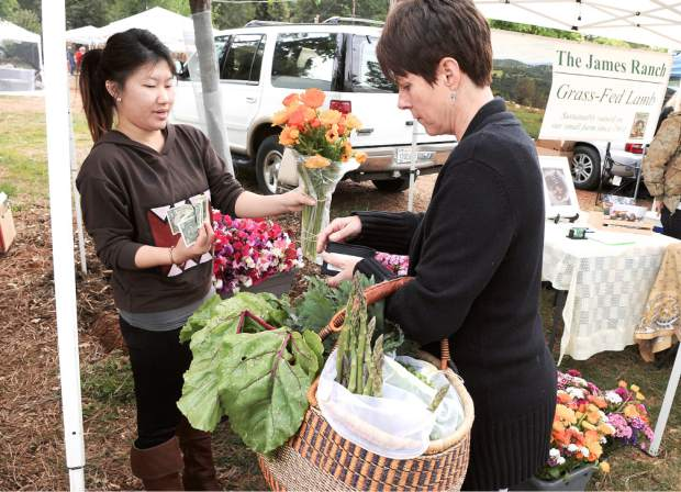 The first Nevada County Certified Growers Market was held Saturday morning at the North Star House, Auburn Road in Grass Valley. Other farmers' markets will also open soon, starting May 5 at the Rood Center, and May 7 in Penn Valley. Pictured is Kathryn Haynes with a basketful of vegetables, while buying fresh flowers from Lucy Xiong.