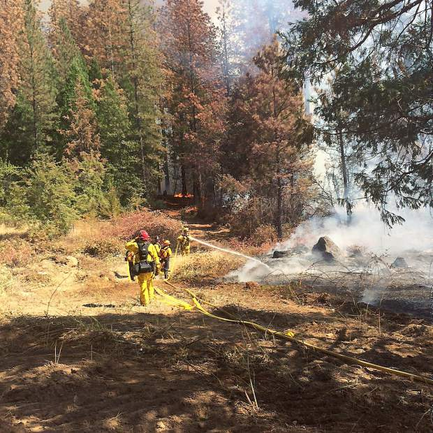 Firefighters work to create a break line for a vegetation fire in Grass Valley that consumed more than 40 acres, spreading quickly through dead trees killed by bark beetle infestation.