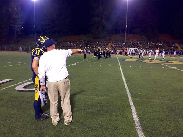Nevada Union coach consulting a palyer near the sidelines Friday night, against the Lincoln Fighting Zebras.