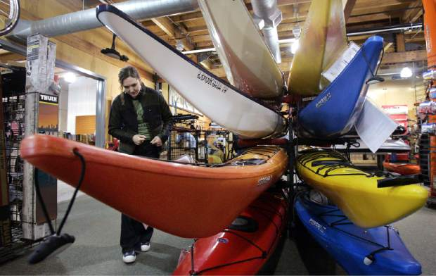 FILE - In this March 13, 2006 file photo, Rachel Hartman looks over sea kayaks as she shops for a birthday present for herself at Recreational Equipment, Inc. store in Seattle. The outdoor retailer, known as REI, has announced it will buck Black Friday 2015 and close its 143 stores on the day after Thanksgiving. The Kent-based co-op told members the plan in an email Monday, Oct. 26, 2015 saying instead of working they'll pay their employees on Nov. 27 to be outside. (AP Photo/Elaine Thompson)