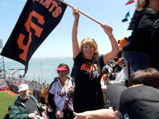 Karen Campbell waves her Giants flag during last season's bus trip to San Francisco. Campbell has been planning an annual bus trip to a Giants game for the last seven years and will be taking 150 fellow fans with her this year.