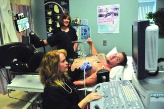 Echocardiographer Brandy Broyer operates a machine that monitors the heart of Daniel Whiteman, echo tech, as SNMH Foundation Executive Director Kimberly Parker looks on. Such equipment was funded by SNMH Foundation.