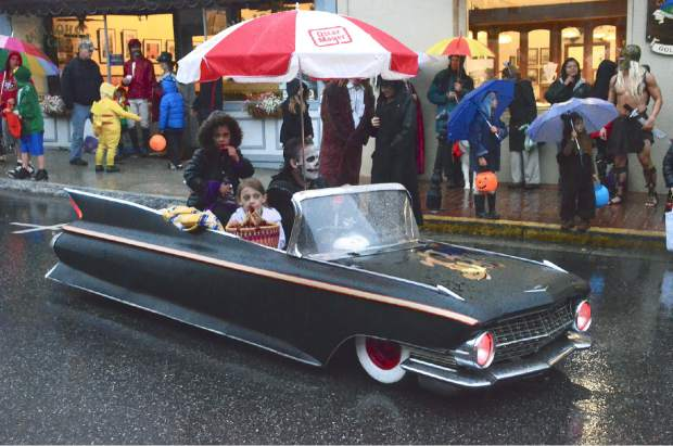 A small car with a large umbrella drives the parade route in  Nevada City's 2014 Halloween Parade on  Broad Street..
